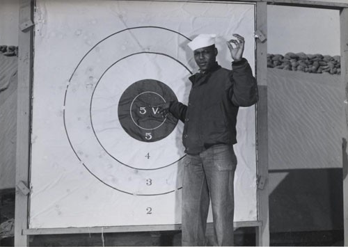 """Naval Air Station Paco, Washington, bluejacket C. Williams, Seaman Second Class, USNR, checking his shooting pattern at the outdoor range on the station."""