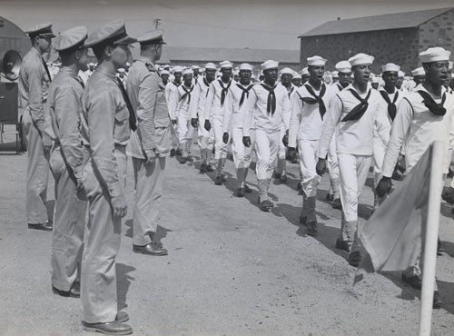 """A company of Negro recruits sing one of its own marching songs as it passes Lieutenant Commander Daniel W. Armstrong, commanding officer of Camp Robert Smalls, and his staff during a military review."""