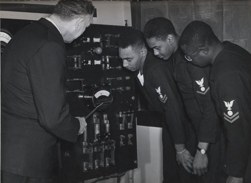 """Electrician's Mates (left to right) Nathaniel O. Dyson, Second Class; Richard Hubbard, Third Class; and John W. Reagan, Second Class, listen as Chief Electrician's Mate John E. Taylor, USN, (Ret.), explains the workings of the power system and distribution process they'll be working with when serving aboard a DE [destroyer escort]."