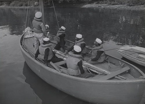 """'Learning sail' - Modern sailors of Uncle Sam's steam and diesel Navy still learn sailing tactics as part of their training. These Negro seamen, part of the 128 who recently arrived at historic Hampton Institute, Virginia, for training as Navy Petty Officers, are getting a few pointers from a Chief Boatswain's mate."""