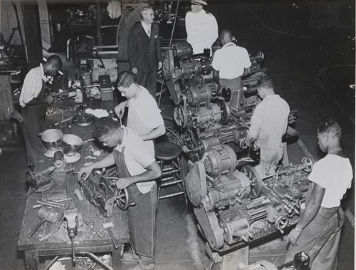 """Machine Shop at Hampton Institute, Virginia. Dr. Malcolm S. MacLean, president, and Lieutenant Commander E.H. Downes, USN (Ret.), watch regular students of the Institute at work."""