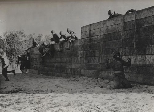 """'Up and at 'em' - Undergoing a stiff training course in order to get in trim for stern duties ahead, Negro Seabees hurdle a high fence as one feature of a trying obstacle course. One of them came down on his knees - but by the wide grin he wears, he is unhurt, will soon be up and off."""