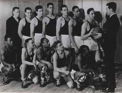 """Chief Specialist John J. Gilmartin is shown giving members of his US Naval Hospital basketball team last minute instruction before a game. Back row, (left to right), Werling, Sinager, Morin, Wilson, Fairchild, Fouse, Johnson. Front row (left to right), Pickett, Anderson, Thomas, Duff, Williams, and Coach Gilmartin."""