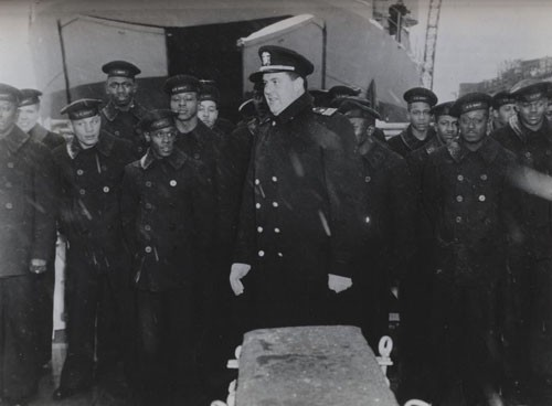 """Skipper and some of the Negro sailors of the USS Mason - destroyer escort, first US Naval vessel with a predominantly Negro crew, at the ship's commissioning ceremony this afternoon at Boston Navy Yard. Lieutenant Commander William M. Blackford, USNR, who assumed command of the vessel and his men smile despite driving snow."
