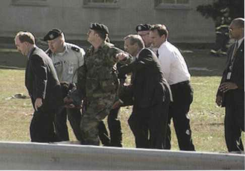 Secretary Rumsfeld (foreground, second from right) assists with carrying a victim on a stretcher toward an ambulance on Route 27.