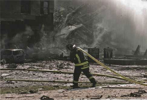 Fort Myer firefighter Vance Valenzo carries a hose across the debris-covered Helipad.