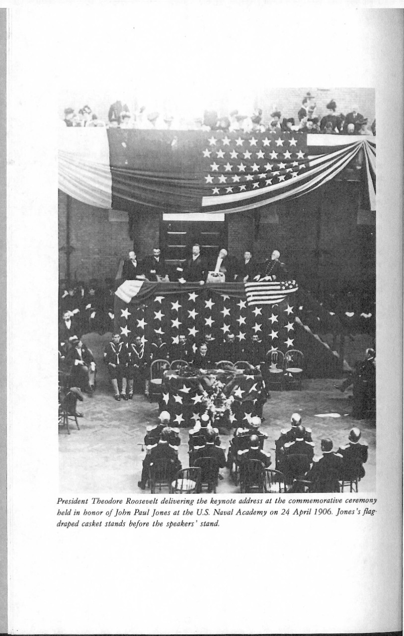 President Theodore Roosevelt delivering the keynote address at the commemorative ceremony held in honor of John Paul Jones at the US Naval Academy on 24 April 1906. Jone's flag draped casket stands before the speakers' stand.