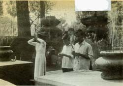 "Common Vietnamese gesture of worship, the ""lay"" (pronounced ""lie"") is performed by woman at left with joss sticks in clasped hands."