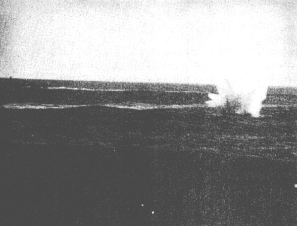 Image of Japanese dive bomber crashes off starboard bow of Enterprise.