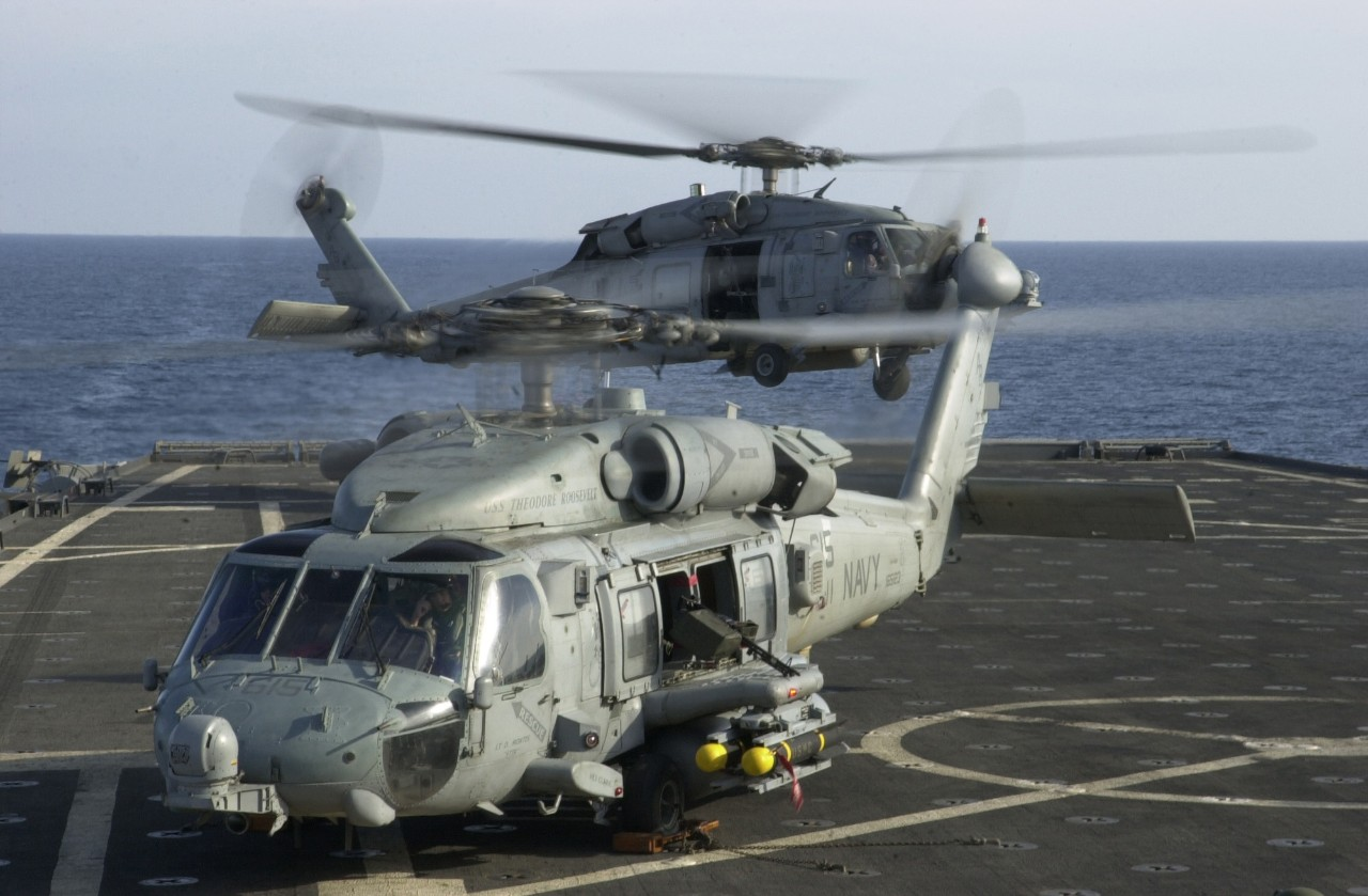 jpeg showing two HH-60H Seahawk helicopters from the Dragon Slayers of  Helicopter Anti-Submarine Squadron One One (HS-11) lift off from the flight deck of USS Shreveport.