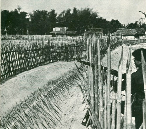 Image - A guard patrols the defenses of a fortified village protected by sharpened bamboo stakes.