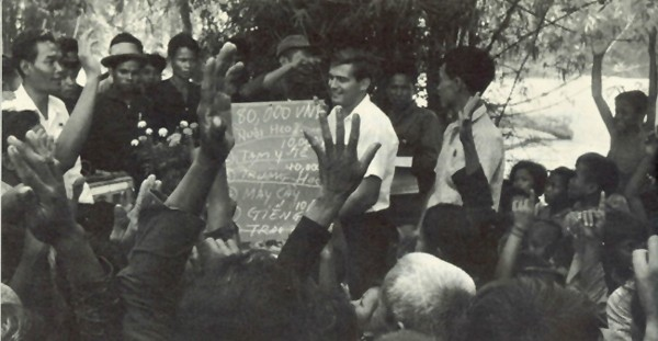 Image - South Vietnamese villagers vote on the use of the community development budget of 80,000 piasters allocated by the provincial administration. An AID field representative holds a blackboard listing the items voted on. They include pig raising, health station, schoolhouses, tractors, wells, and buffaloes.