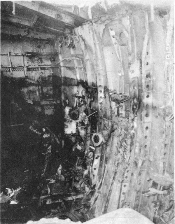 Photo 12: Damage to after port side of bulkhead 86-1/2. Note top of bulkhead pulled away from main deck.