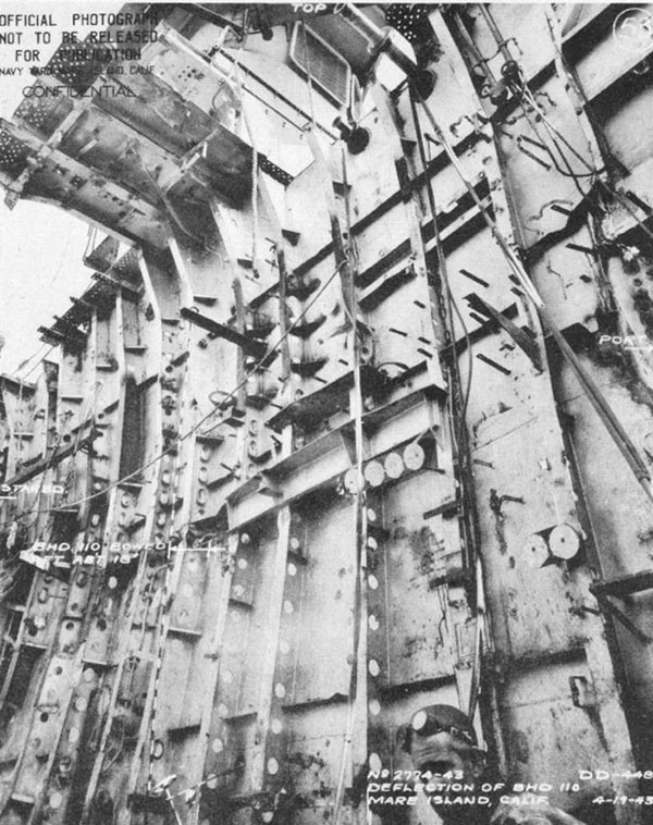 Photo 25: Bulkhead 110 after removal of debris from forward engineroom; deflection due to torpedo blast and static water head.