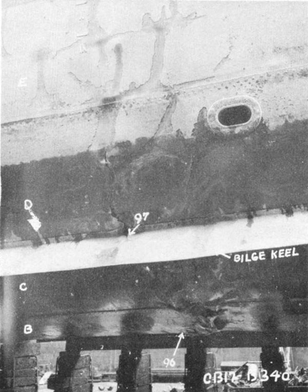 "Photo 7: Starboard side view of damage to shell. Note failures in ""B"", ""C"", and ""D"" strakes and buckles in ""E"" strake."