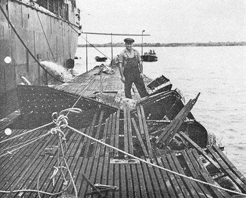 Photo 9-2: SCAMP (SS277). Bomb damage to superstructure. Alongside TANGIER (AV8), Seeadler Harbor, Admiralty Islands.