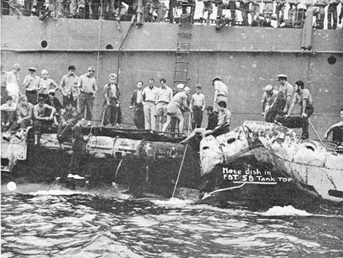 Photo 9-3: SCAMP (SS277). View from port side, showing bomb damage to superstructure. No structure has been removed yet.