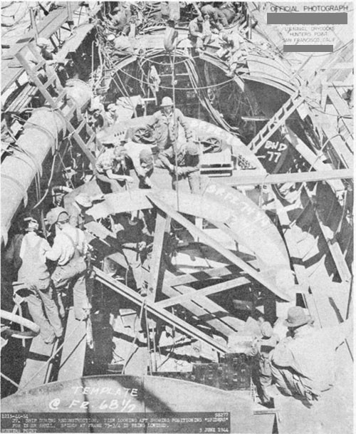 "Photos 9-14 and 9-15: SCAMP (SS277). Two views showing reconstruction of damaged portion of ship at U. S. Naval Drydocks, Hunter's Point. Note positioning ""spiders"" for pressure hull shell plating."