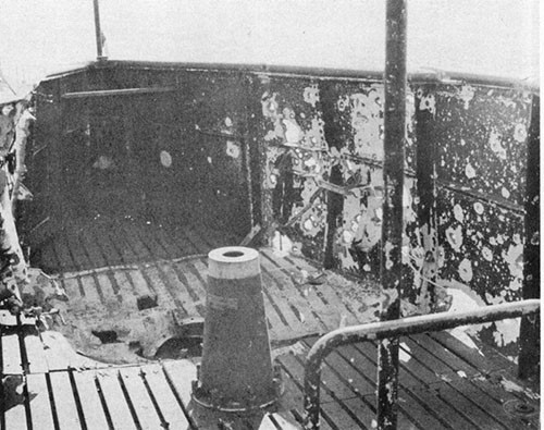 Photo 12-2: GRAMPUS (SS207). View showing fragmentation damage. Projectile is believed to have detonated approximately over the outboard engine air induction valve about two feet above the cigarette deck.