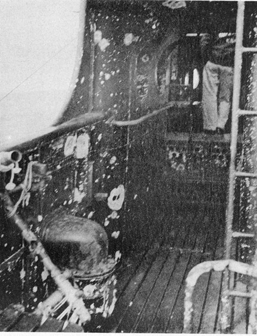Photo 12-3: GRAMPUS (SS207). Fragmentation damage, port bulwark forward end of cigarette deck.