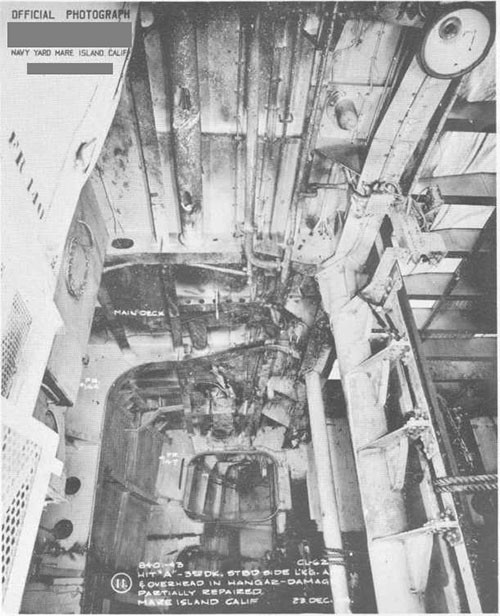 Photo 7: Bomb damage to stern. Looking aft and to overhead in Hangar. Damage partially repaired.