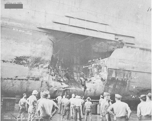 Photo 10: Torpedo damage, port side. Note temporary patch at top of hole.