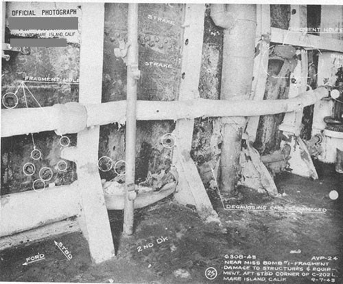 Photo 2: Fragment holes resulting from bomb No. 1. Note torn degaussing cables and buckled beam brackets.