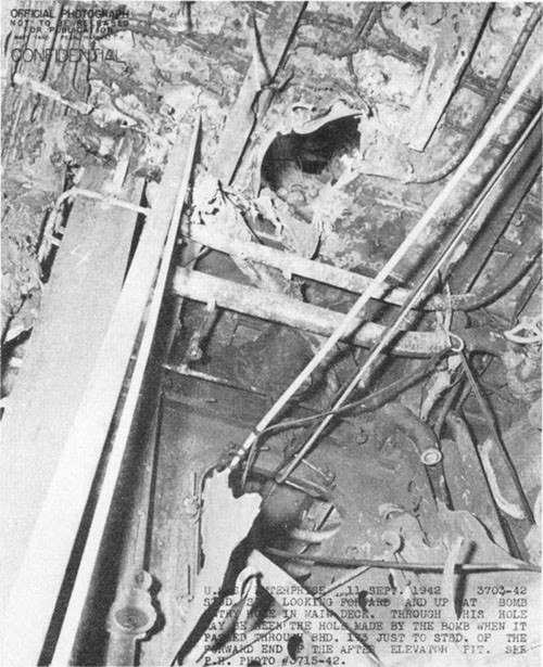 Photo E-3: First hit. Looking aft and upward from compartment D-203-1LM through bomb passage hole in main deck to bomb passage hole in bulkhead 173 between the main and gallery decks.