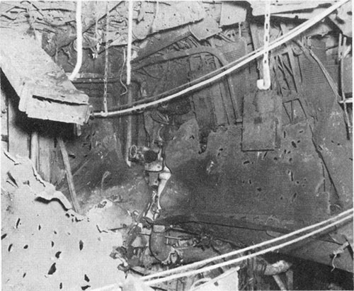Photo E-4: First hit. Bomb hole in second deck, compartment D-203-1LM. Note fragment holes.