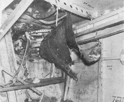Photo E-5: First hit. Compartment D-419-A, starboard after corner looking outboard. Note bomb hole in third deck and shoring and mattresses used to stop leak in shell just below the fourth deck.