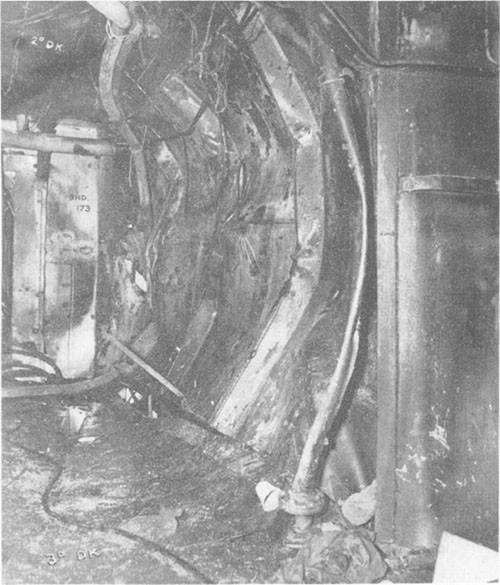 Photo E-7: First hit.  Compartment D-303-1L looking aft showing starboard bulkhead of No.3 elevator pump room (D-523-T) dished in to port, third deck dished down and second deck dished up.
