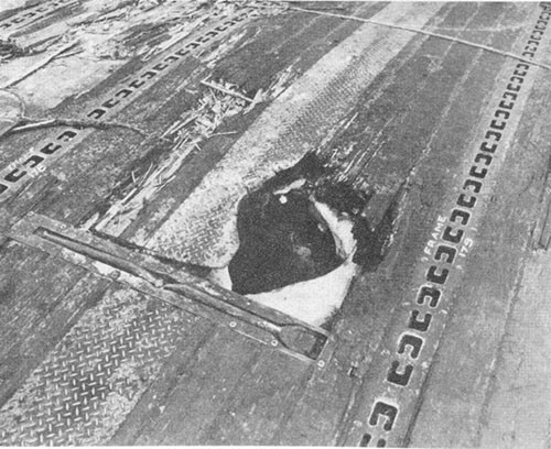 Photo E-13: Second hit. Entrance hole in flight deck made by bomb.