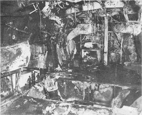 Photo E-15: Second hit. View of 5-inch Group III gun gallery looking forward showing damage in gallery deck and inboard bulkhead by explosion of bomb and burning of 5-inch ready-service ammunition.