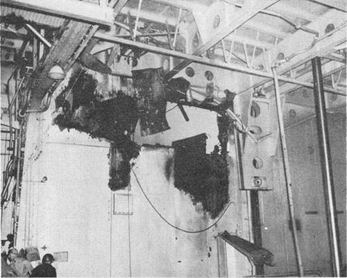 Photo E-16: Second hit. Looking outboard from No. 3 elevator trunk through hole blown in inboard bulkhead of Group III gun gallery by explosion of bomb and burning of 5-inch ready-service ammunition.