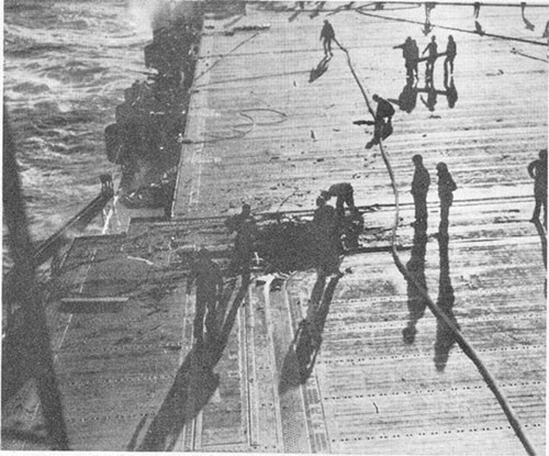 Photo E-17: Third hit. View of flight deck showing bomb hole near after starboard corner of No. 2 elevator.