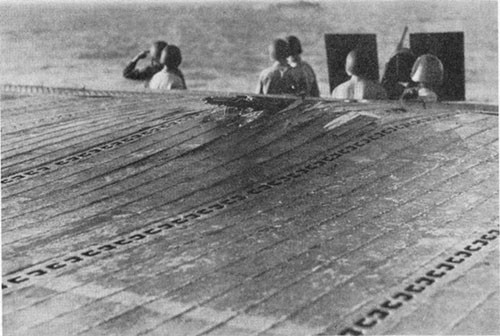 Photo E-20: Near-miss. Damage to extreme after port corner of flight deck caused by water column from the near-miss.