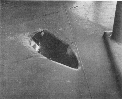 Photo F-2: First hit. Bomb passage hole in port side of forecastle deck.