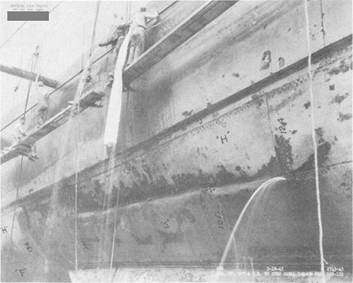 Photo F-11: First near-miss. Starboard side frames 123-135 in way of detonation. Note wooden plugs driven into rivet holes by divers.