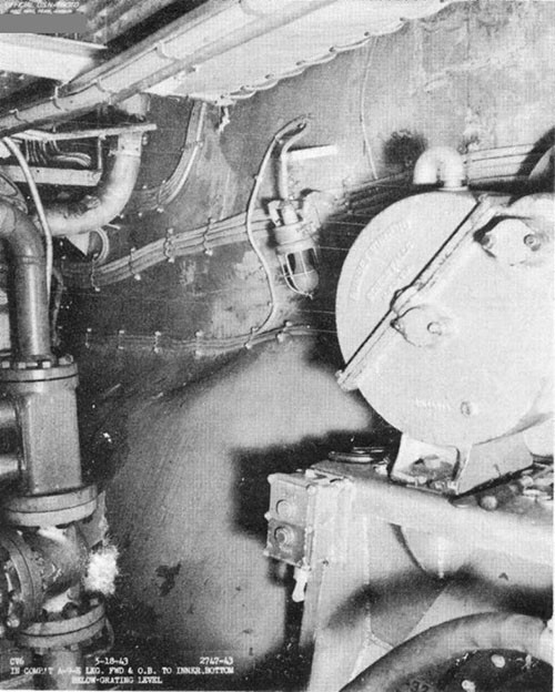 Photo F-24: Second near-miss. Deflected inner bottom plating in A-9-E, looking forward on starboard side.