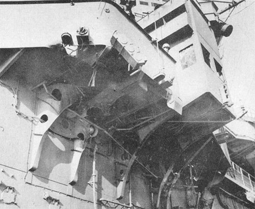 Photo H-2: Dud hit. Port side of island and navigating bridge showing brackets broken by passage of bomb.