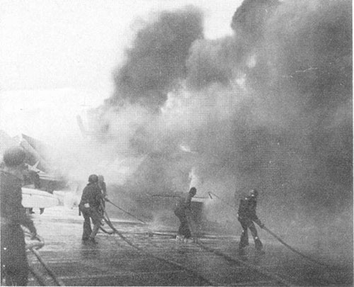 "Photo H-4: ""Friendly"" shell hit. Parked planes on fire. Note use of low velocity fog applicator to protect man with foam hose."