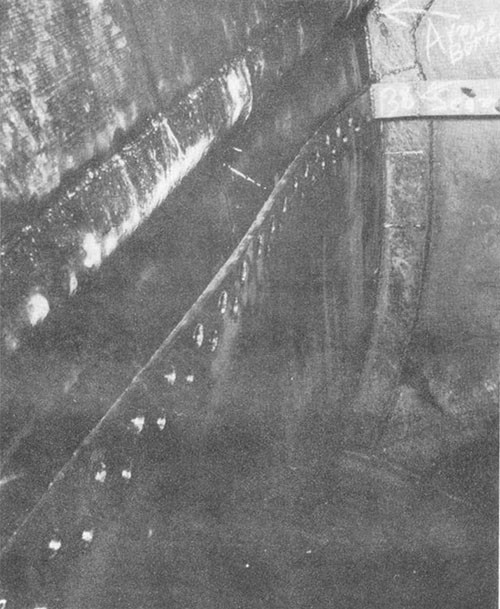 Photo I-3: First near-miss. Riveted seam below armor belt inside blister tank D-54-F, ruptured a: a result of bomb detonation.