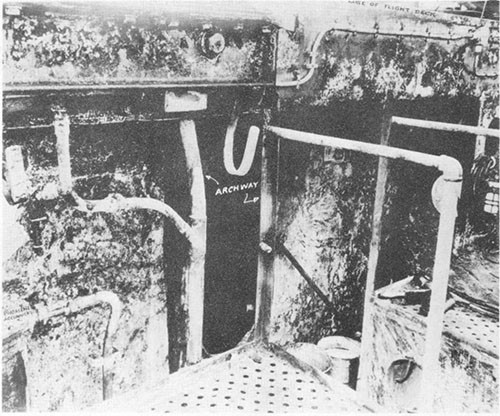 Photo C-2: Charred paint on bulkhead, port gun gallery. Archway and ladder are between frames 140 and 141. Phomene accumulator at extreme left.