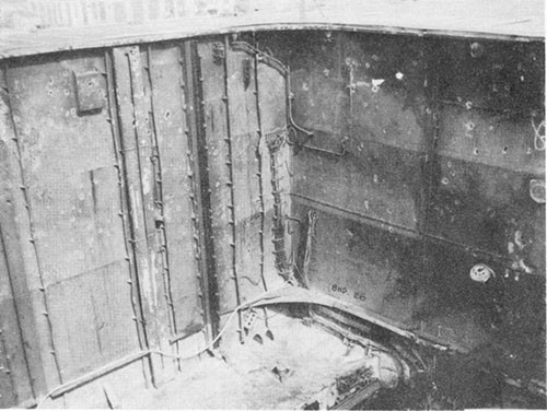 Photo J-6: View looking to port and forward in No. 1 elevator trunk after debris cleared up. Note dishing of bulkheads and fragment holes.