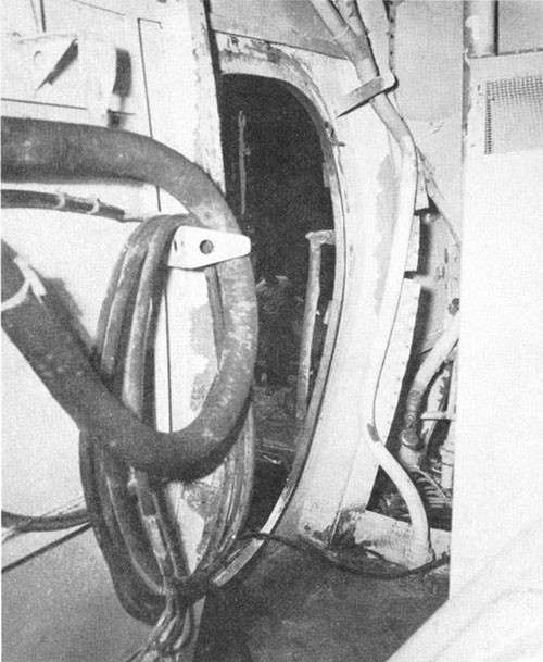 Photo J-7: Frame of quick-acting, watertight door 1-26-1 between A-104-1L and No. 1 elevator trunk. Door was blown out of frame.