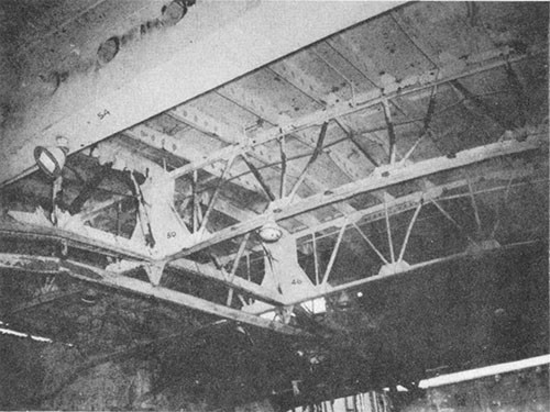 Photo J-9: Overhead of hangar deck looking forward and to port showing bulge in flight deck frames 58 to 26. Note buckling of girder struts in bents at frames 46 and 50.