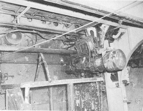 Photo J-15:  Looking aft and to starboard, port 5-inch gun platform showing damaged flight deck elevator trunk stanchion motor.