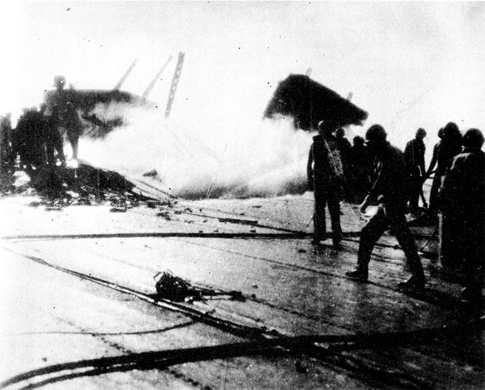 Photo 2: 30 October Action. Flight deck looking starboard and aft, showing damage at frames 125-128.