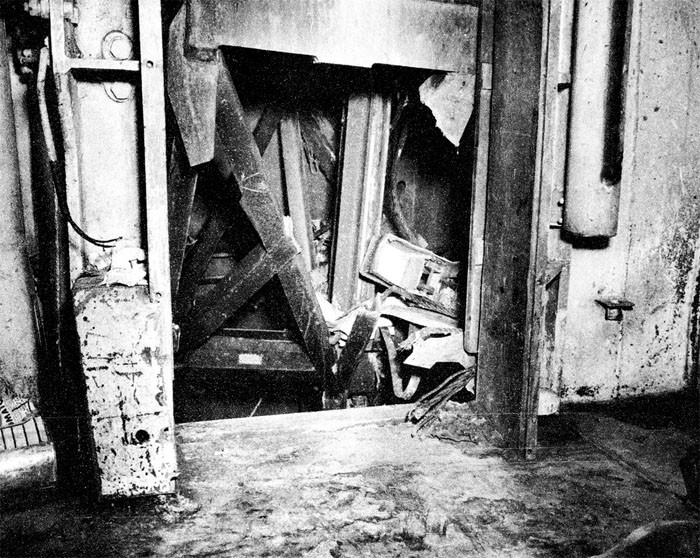 Photo 9: 30 October Action. View showing damaged bomb elevator, B-0435-T, and damaged watertight door 3-128-1 as seen from B-318-L, crew's galley, looking forward.