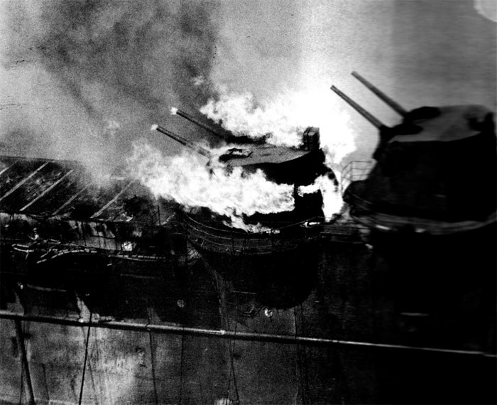 Photo 19: 19 March Action. Ammunition in No. 7 twin mount is burning. This occurred late in fire. Note that fire on flight deck aft is about out.